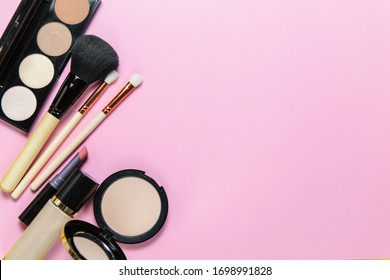 Makeup brushes, powder, eyeshadow palette, foundation for the face on a light pink background with place for text, top view - Shutterstock ID 1698991828