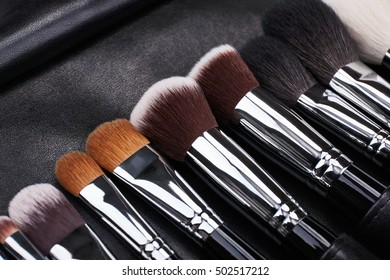 Makeup brushes set on black leather background.