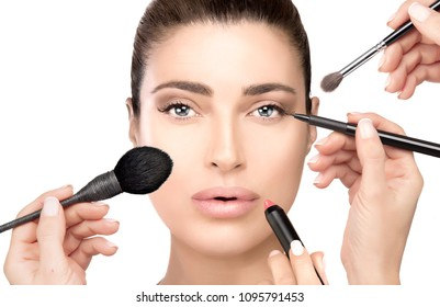 Makeup concept. Front view on gorgeous brunette model girl with hands reaching toward her face to apply makeup with various tools. Make-up process