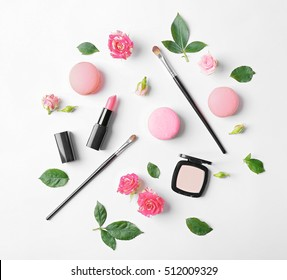 Makeup cosmetic with macaroons and beautiful flowers on white background