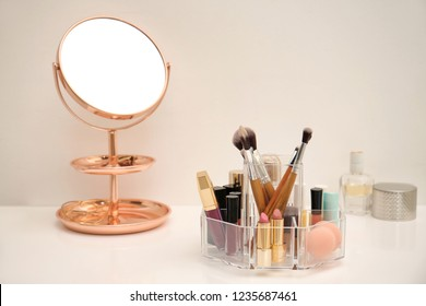 Makeup cosmetic products and tools in organizer on dressing table
