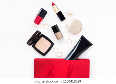 Makeup cosmetic products for woman in gift red bag on light background