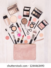 Makeup cosmetics and accessories and an open bag on white wooden background, top view with copy space