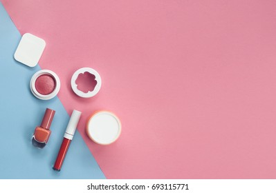 makeup cosmetics, brushes and other essentials on pink and light blue background top view. beauty flat lay concept in red colors with copy space