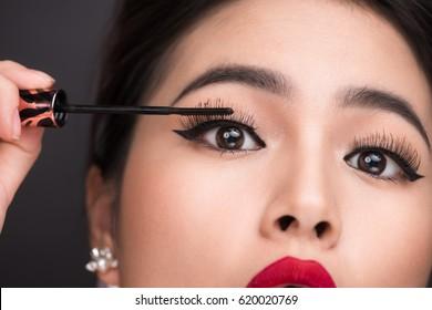 Make-up and cosmetics concept. Asian woman doing her makeup eyelashes black mascara.
