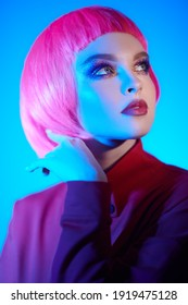Makeup cosmetics and hairstyle. Portrait of a beautiful young woman with bright glitter makeup and pink hair posing in mixed color neon light. Beauty trends.