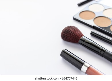 makeup cosmetics on white table with over light and soft-focus in the background