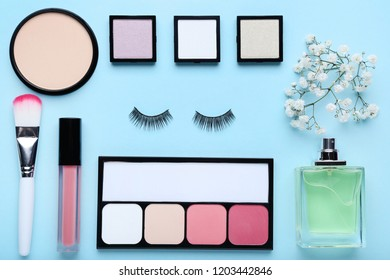 Makeup cosmetics with perfume bottle and eustoma flowers on mint background
