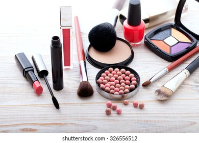 Makeup cosmetics products on white wooden background, copy space. Cosmetics make up artist objects: lipstick, eye shadows, eyeliner, concealer, nail polish, powder, tools for make-up. Selective focus