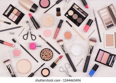 Makeup cosmetics such as eyeshadows, lipstick, mascara and other on white, wooden background, top view