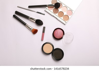Makeup cosmetics tools background & beauty cosmetics, products & facial cosmetics package lipstick, spatula, blush brush, powder brush, compact powder, blush & highlighter palette on white background.