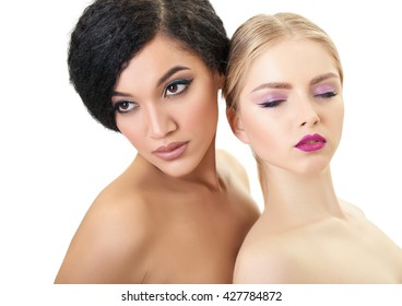 Makeup. Double female portrait. Caucasian blond girl and beautiful mulatto young woman posing in studio over white background. Fashion, beauty, glam, youth.