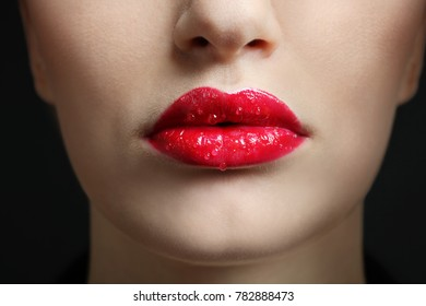 Makeup, drops on the lips with red lipstick. Close-up.