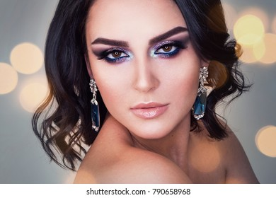 Makeup. Elegant hairstyle. Beautiful brunette smiling with wavy hair, makeup and fashion jewelry earrings. Attractive girl.