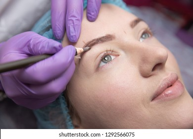 make-up for eyebrows of beautiful woman with thick brows in beauty salon. Closeup beautician doing tattooing eyebrow.