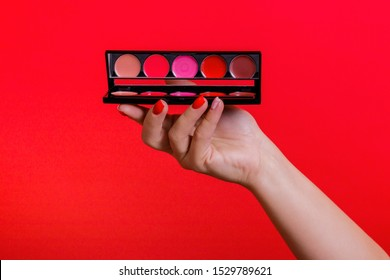 Makeup eyeshadow palette in female hand on the red background. Make-up eyeshadow palette set.