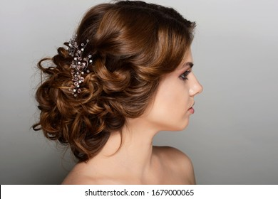 makeup and hairstyle portrait young girl on a white gray background light brown natural hair color natural makeup gathered hair curls curled hair jewelry accessory feminine image for the bride