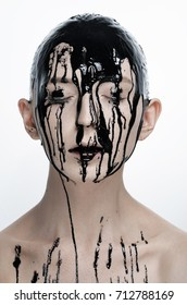 Make-up and halloween theme: beautiful girl model with liquid black paint oil on face on white isolated background