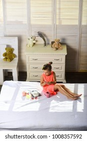 Makeup and kids fashion concept. Little girl takes tea and plays with moms cosmetics. Kid wears bright dress and holds cup in room with teddy bears. Girl smiles and drinks tea on bed in childroom.