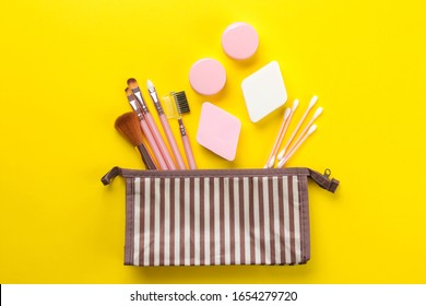 makeup kit. Female makeup brushes in a cosmetic bag on a yellow bright background. women things. top view