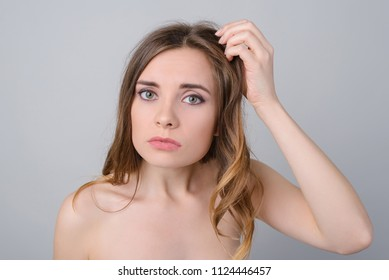 Make-up lack of vitamins minerals quick dirty hairstyle concept. Close up photo portrait of sad upset troubled lady holding brittle unhealthy brunette dyed curls in hand isolated on grey background