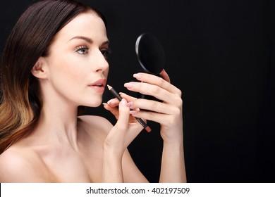 Makeup, lip makeup.Woman performs makeup, paints lips liner pencil