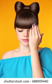 Makeup. Manicure. Hairstyle. Beautiful teen girl with bow hair style and multicolor manicured polish nails. Funny girl showing fingers isolated on yellow background.
