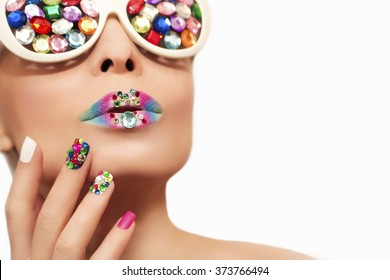 Makeup and manicure with multicolored crystals and glasses on the blonde girl.