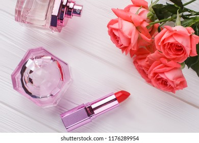 Makeup materials and flowers, flat lay. Perfume, lipstic and rose flowers. Top view.