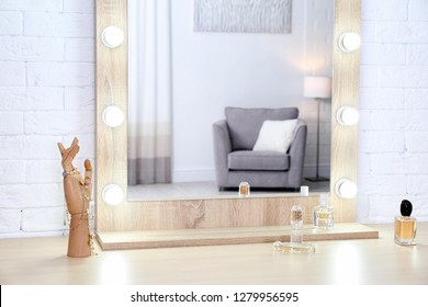 Makeup mirror on table near white wall in dressing room