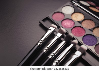 Makeup moody background. Eye shadows palette and brushes. Trendy colors, minimal composition. Copy space for your text.