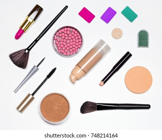 Makeup must haves. Basic contents of cosmetic bag. Concealer stick, foundation, powder, blush, eyeliner, mascara, eyeshadow, lipstick, make-up brushes and sponge