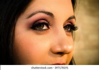 Makeup on a beautiful woman. Eyes makeup.  Partial facial woman's photo, with intentional blur on background. Purple eye makeup.