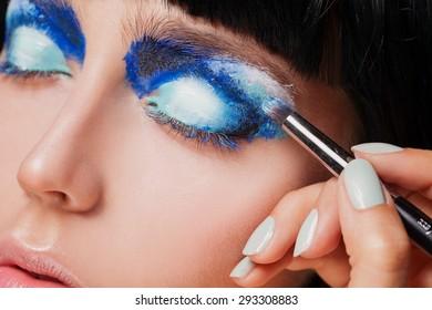 Makeup. Make-up. Painting blue eyeshadows. Eye shadow brush. Close up