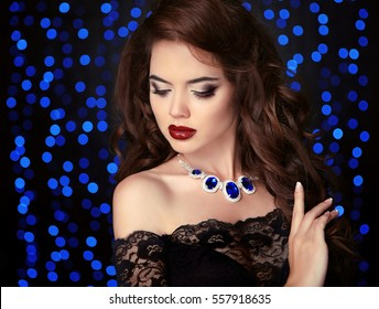 Makeup. Portrait of elegant brunette woman with make-up, healthy curly hair style and necklace jewelry over blue bokeh party lights ob black background.