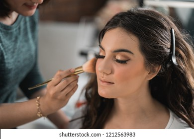 Make-up process, the face of a beautiful young woman and makeup artist's hand with a brush and sponge