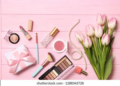 makeup products and beautiful spring flowers on wooden background. Top view.