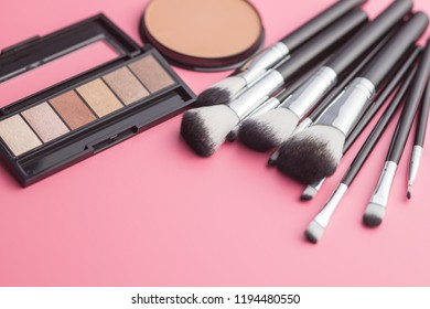 The makeup products. Brush and eyeshadow powder on pink background.