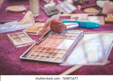 Makeup products and brushes spread out on table