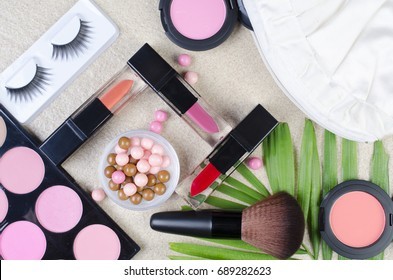 Makeup products with cosmetic bag top view on a sandstone background.