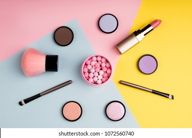 Makeup products and decorative cosmetics on color background flat lay. Fashion and beauty blogging concept. Top view