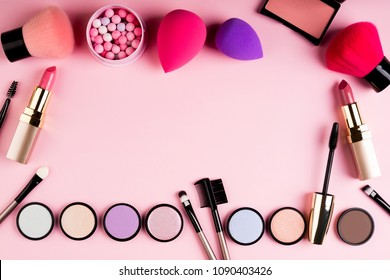 Makeup products and decorative cosmetics on pink background flat lay. Fashion and beauty blogging concept. Top view, copy space