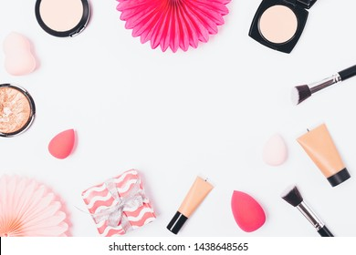 Makeup products and gift box with paper decorations on white background, festive flat lay frame.