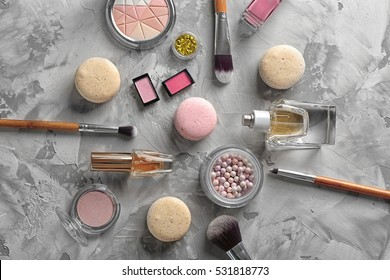 Makeup products and macaroons on grey textured background