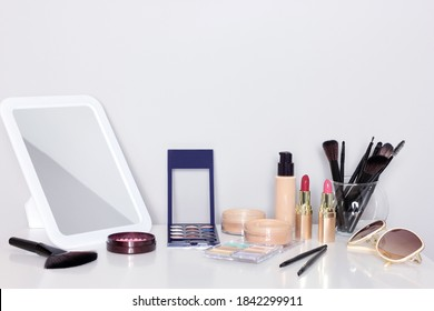 Make-up products with mirror on dressing table. Vanity table with makeup accessories