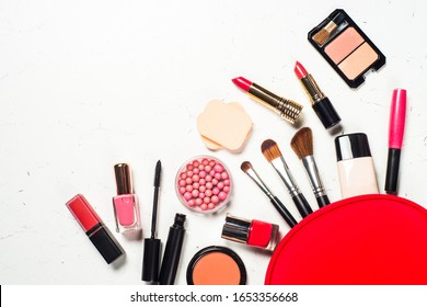 Makeup professional cosmetics with red cosmetic bag on white marble background. Flat lay image with copy space.