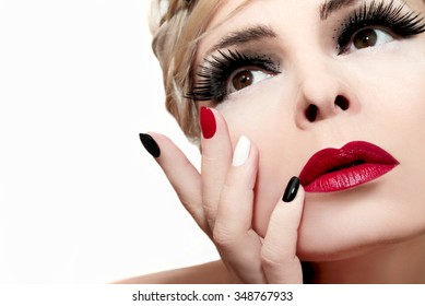 Makeup with red lips,bushy eyebrows,false eyelashes and colored nails.