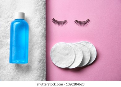 Makeup remover, false eyelashes and cotton pads on color background