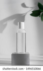 Makeup remover, natural moisturizing lotion mockup close up. Transparent liquid container side view. Organic cosmetics poster concept. Micellar water bottle and blurred leaves on background