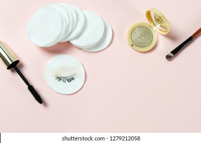 Make-up removing, dirty cotton pads, mascara and eye shadows on pink background. Top view, copy space